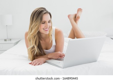 Smiling pretty young woman using laptop in bed at home