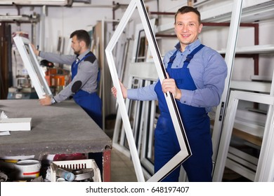 Smiling production workers in coverall with different PVC windows and doors