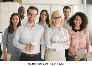 Smiling professional business coaches leaders mentors posing together with diverse office workers interns group, happy multicultural staff corporate employees people looking at camera, team portrait