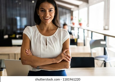 Smiling professional businesswoman in casual, with arms crossed standing in office