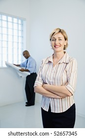 Smiling professional businesswoman standing as man reads architectural plans in background.