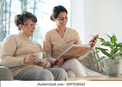 Smiling professional caretaker showing a family album to an elder woman in a living room at home