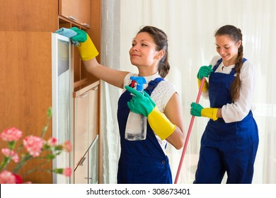 Smiling professional cleaners team cleaning in the house with rags and mop. Selective focus