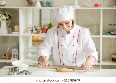 Smiling professional confectioner rolling thing gingerbread dough. Lifestyle image. Baker self-employed woman wearing uniform making sweet cookies in her small workshop indoors