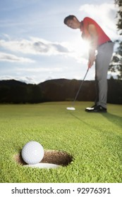 Smiling professional male golf player putting successfully ball on green with close up of ball dropping into cup.