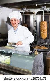 smiling professional  man chef in uniform serving fresh kebab in restaurant
