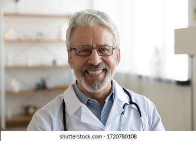 Smiling professional older man doctor wears white coat, glasses and stethoscope looking at camera. Happy bearded senior physician or therapist with dental smile posing for close up head shot portrait.