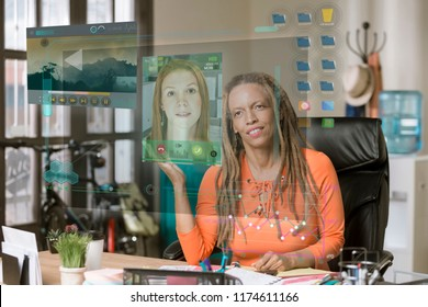 Smiling professional woman using a futuristic communication screen in her office