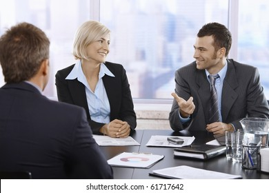 Smiling professionals sitting and talking in meeting room in skyscraper office.?