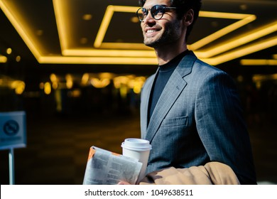 Smiling prosperous stylish man in elegant suit and spectacles holding newspaper standing near neon light, positive successful male entrepreneur walk with coffee to go and daily press on urban setting