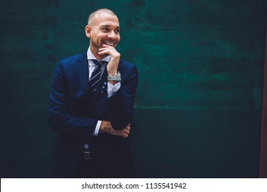 Smiling and prosperous young man entrepreneur looking away while standing against wall with copy space area for your business advertisement or financial information.Successful trader in formal wear