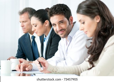 Smiling proud business man looking at camera with satisfaction and working colleagues in office