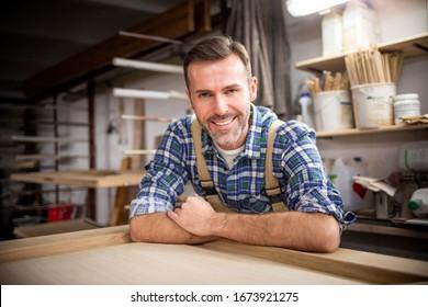 Smiling and proud mature carpenter in his carpentry workshop