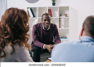 Smiling psychiatrist talking to divorcing couple in office