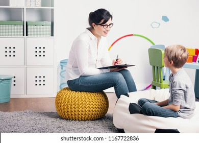 Smiling psychologist talking with kid during meeting in the classroom