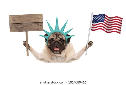 smiling pug puppy dog holding up American flag and blank wooden sign, wearing lady Liberty crown, isolated on white background