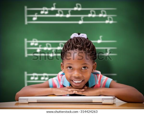 Smiling pupil sitting at her desk against green chalkboard