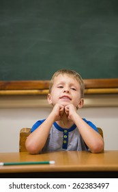Smiling pupil sitting at his desk at elementary school
