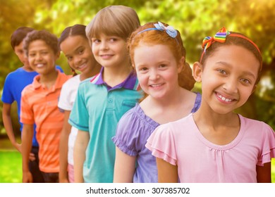 Smiling pupils in classroom against trees and meadow in the park