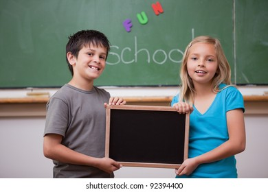 Smiling pupils holding a school slate in a classroom