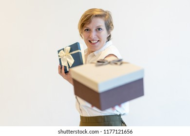 Smiling pushy saleswoman giving gift box to camera. Content confident mature lady selling Christmas presets and looking at camera. Sales manager concept