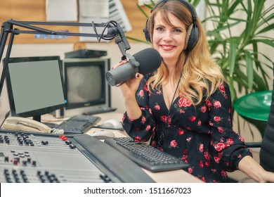 Smiling radio host speaks through a microphone