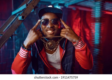 Smiling rapper with gold chain posing in studio