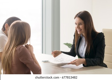 Smiling real estate agent offering to young couple to buy a cottage while meeting at office, presenting technical documentation such as building house plan, telling about advantages of country living