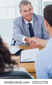 Smiling real estate agent shaking hands with his new buyer in bright office