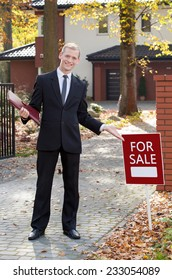 Smiling real estate broker standing in front of new home