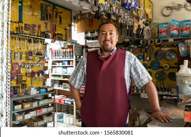 Smiling real worker attending a hardware store. interior detail