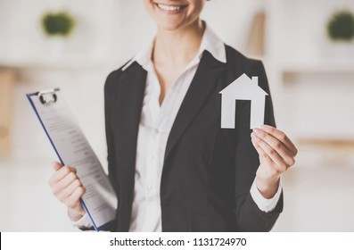 Smiling Realtor Holding Tablet and Paper Model of House. Real Estate Sales Concept. Getting Access to Home Concepts. Investment and Buying Property Concepts. Real Estate Realtor Work.