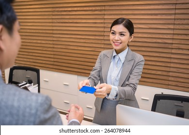 Smiling receptionist giving electronic keys to the guest