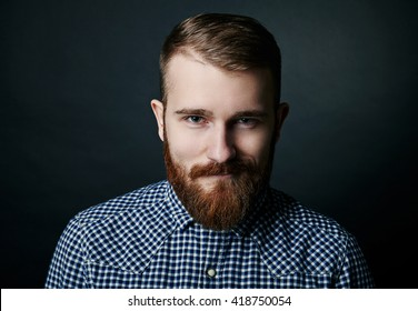 Smiling red bearded man studio portrait on dark background