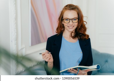 Smiling red haired female writes notes in notepad, holds diary and pen, wears formal suit,, spectacles, poses indoor, listens advice, makes records in personal pocketbook, prepares for meeting