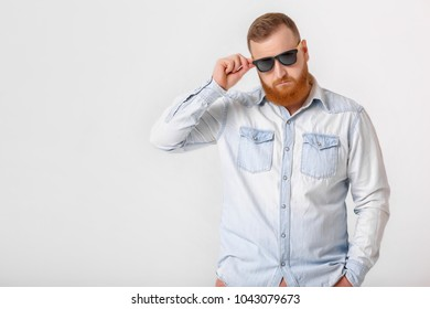 smiling red-haired beard man in sunglasses and denim shirt on gray background. copy space