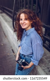 Smiling red-haired girl with a retro film camera