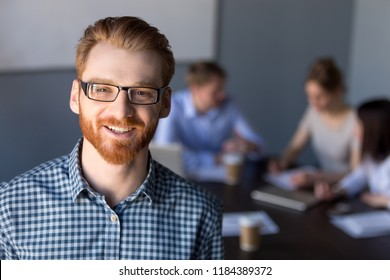 Smiling red-haired millennial business man in glasses looking at camera posing at meeting, young professional employee, team leader, successful entrepreneur, office worker, manager headshot portrait