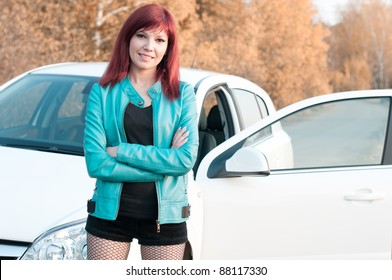 Smiling red-haired young woman standing by her car on an autumn road