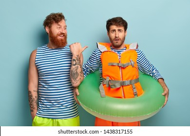 Smiling redhead bearded young man points at friend coward, gives lesson of swimming, spend leisure time together in hot resort place, enjoy summer weekend. Friendship, rest and recreation concept