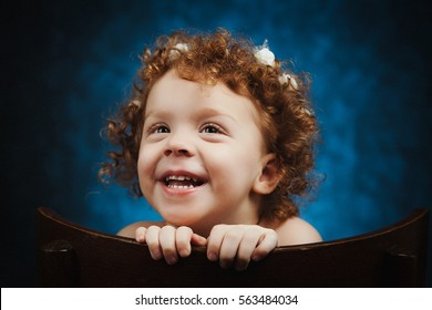 Smiling redhead little girl, with funny face. Cute child with flowers rim on her head.
