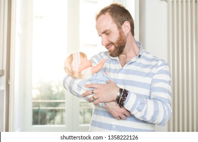 Smiling Redhead Man with Beard  Cradling a Doll