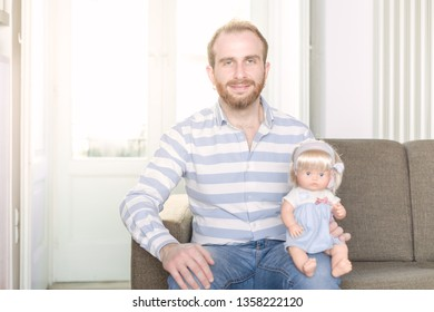 Smiling Redhead Man on a Couch with a Doll Sitting on His Knee