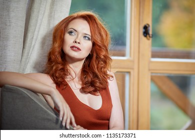 Smiling redhead outdoors backlit by sun, fashion shoot. Close up woman portrait . redhair girl. Beautiful young woman close-up in autumn .