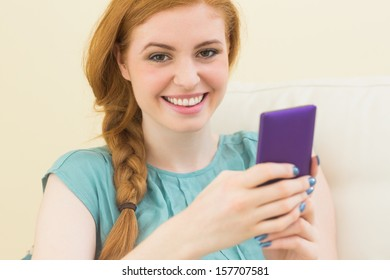 Smiling redhead sitting on the couch using smartphone at home in the living room