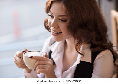 Smiling redhead woman drinking cappuccino in cafe.