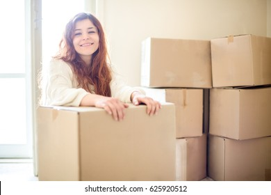 Smiling Redhead Woman Moving with Boxes