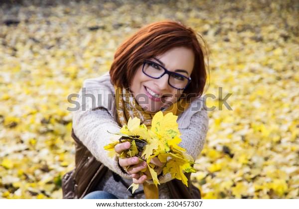 Smiling redhead woman with yellow autumn leaves. Seasonal theme.