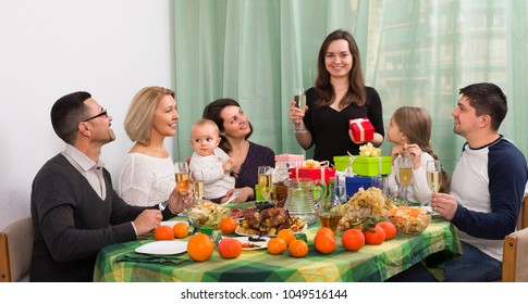 Smiling relatives congratulating family member with gifts and toasts ate the table at home