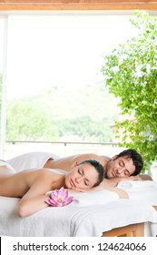 Smiling relaxed couple lying together after a treatment at spa